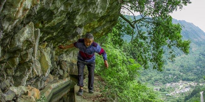 黄大发走在险峻的擦耳岩上,山下是新房林立的村庄(田维野摄)