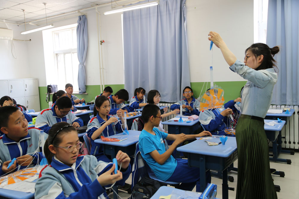 Science teacher Ma Ruihong guides students to make a rocket model at Beijing Xicheng Foreign Languages School on April 26, 2017.