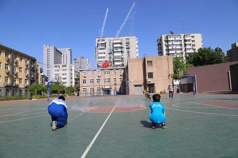 The rocket models are launched into air from the playground at Beijing Xicheng Foreign Languages School on April 26, 2017.