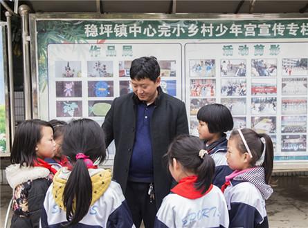张金省(中)慷慨解囊,捐钱给村里的孩子们购买文具,图为张金省和孩子们在一起。图片来源:贵州省文明办