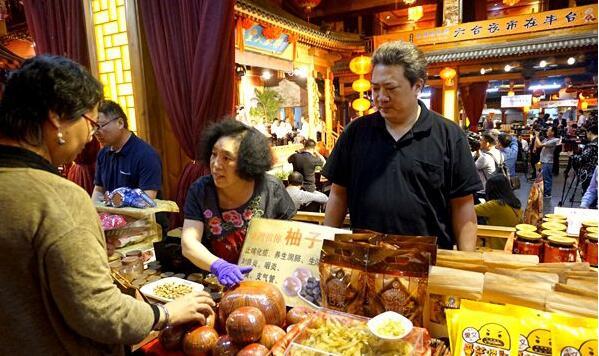 商户向游客介绍台湾特色柚子肉的功效。(中国台湾网 高斯斯 摄)