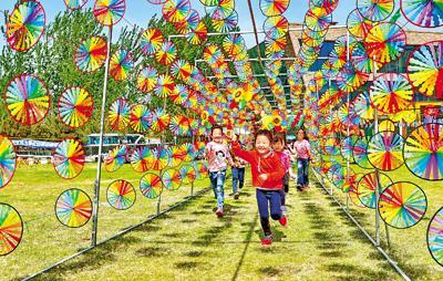 4月29日,少年儿童们在河北省秦皇岛市海港区北港镇紫云山滑雪场风车长廊中游玩。史自强 曹建雄摄影报道