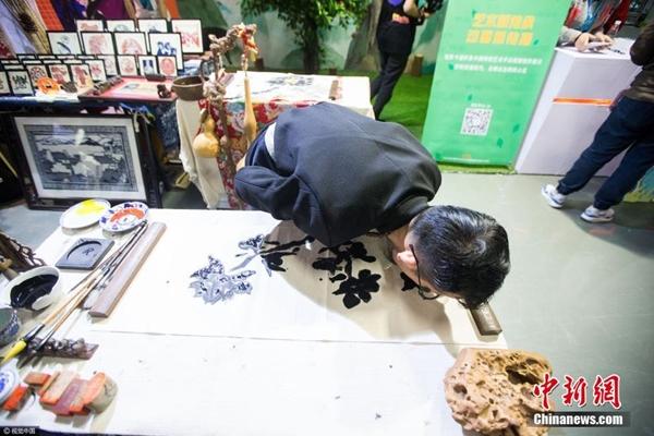 فنان يبدع لوحات فنية بلسانه في هانغتشو