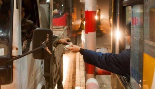 图为收费站收费员在工作时接收司机缴费的钱款