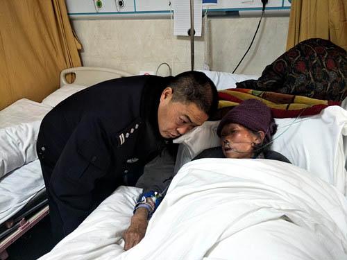图为龙文进在医院照顾患病的潘发芬老人。图片来源:贵州省文明办