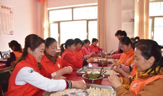 图为雷锋志愿者正在包爱心饺子。