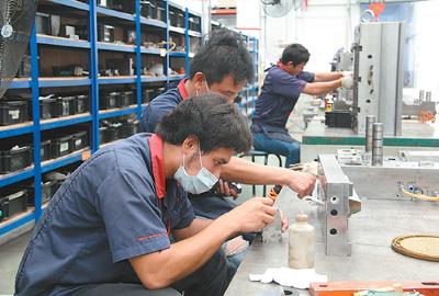 泰国工人在罗勇工业园内的和诚制造(泰国)有限公司车间认真工作。