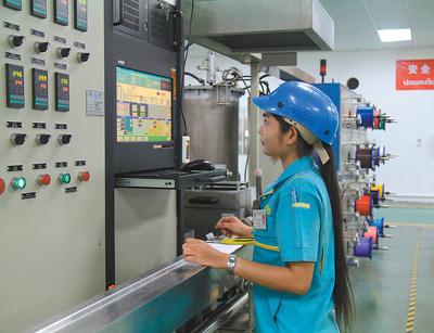在富通集团(泰国)通信技术有限公司车间,泰籍员工正在检测设备生产情况。