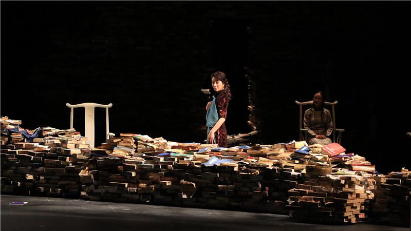 话剧舞台上的城墙改由一摞摞的书本堆砌而成,用诗化的语言讲述战后颓败的小城故事,图为《小城之春》剧照