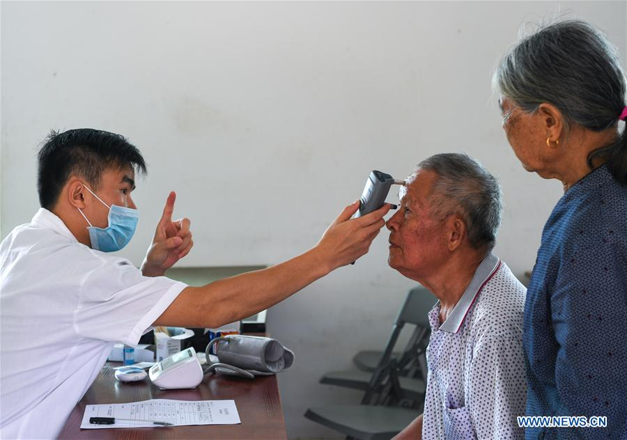 Doctor Li Yahui (L) exams for 76-year-old villager Wang Guangchun in Maozu Village in Wuzhishan City, south China