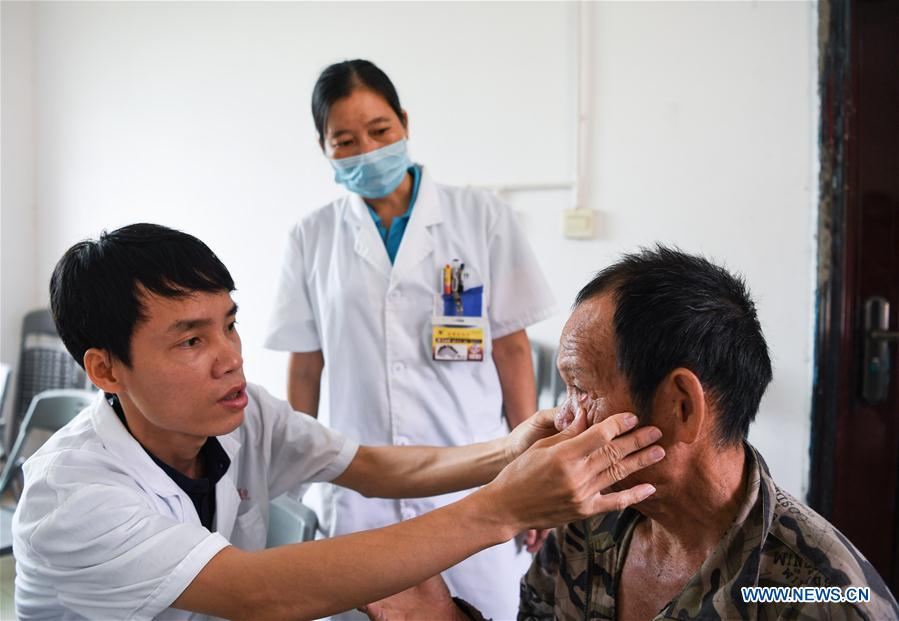 Doctor He Wenyi (L) exams for 66-year-old villager Wang Maohua in Maozu Village in Wuzhishan City, south China