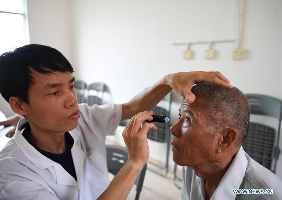 Doctor He Wenyi exams for 64-year-old villager Wang Laoliao in Maozu Village in Wuzhishan City, south China