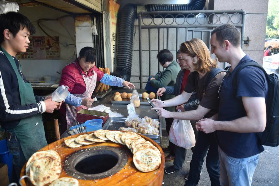 A foreigner scans the QR code to pay for snacks at a food stall in Hangzhou, the capital city of Zhejiang province, on April 14, 2017. [Photo/Xinhua]