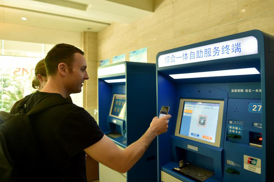 A foreigner pays his medical fees by scanning the QR code on a machine at the Second Affiliated Hospital of Zhejiang University School of Medicine in Hangzhou, Zhejiang province, on April 14, 2017. [Photo/Xinhua]