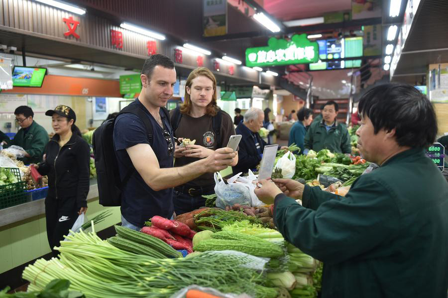 Foreigners experience using mobile payments to buy vegetables at a marketplace in Hangzhou, Zhejiang province, on April 14, 2017. [Photo/Xinhua]