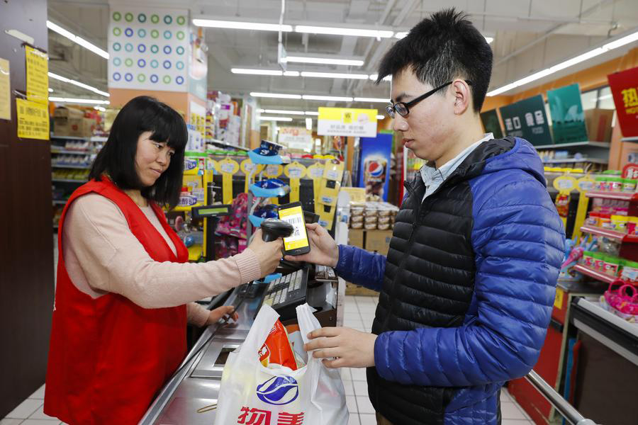 A postgraduate student purchases commodities at a supermarket at the Peking University on March 17, 2017. [Photo/Xinhua]