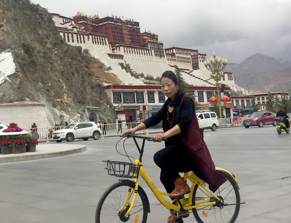 Jamyang Tso, a resident of Lhasa, rides an Ofo bike on Monday near the Potala Palace. [Photo by Palden Nyima/China Daily]