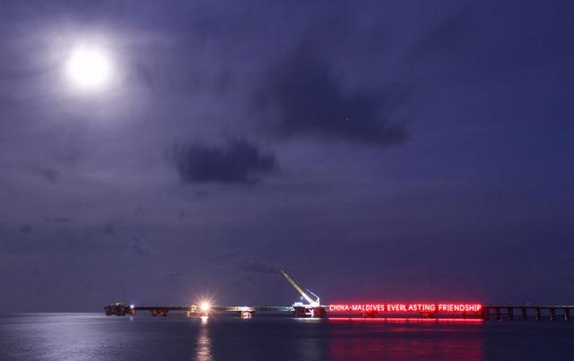 """4月21日,在马尔代夫,建设中的中马友谊大桥上亮起""""中马友谊长存""""的霓虹灯。新华社发(中马友谊大桥项目部供图)"""