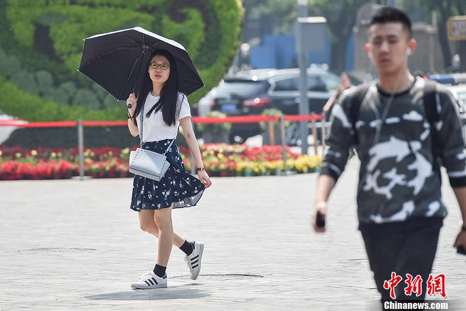 Since May 17, the sun has been grilling Bejing. According to the meteorological department, the temperature could rise to more than 35℃ in Beijing Plain from May 17-19, suggesting the arrival of hottest days in 2017. Photo shows passers-by in summer clothes near Sanlitun, Beijing.