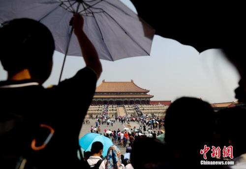 5月18日,游客在北京故宫博物院参观,北京持续高温。中新社记者 杜洋 摄