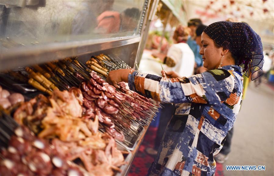 Préparation de kebabs d'agneau dans un marché de nuit au Xinjiang, le 12 mai 2017.