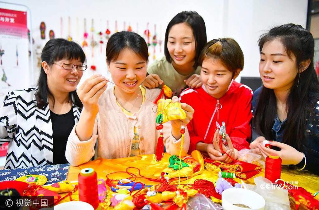 Students from Bozhou College learn to make sachets under the instruction of their teacher Yu Caixia(1st,L)in Zhumeng Community, Bozhou of Anhui Province, May 23, 2017.