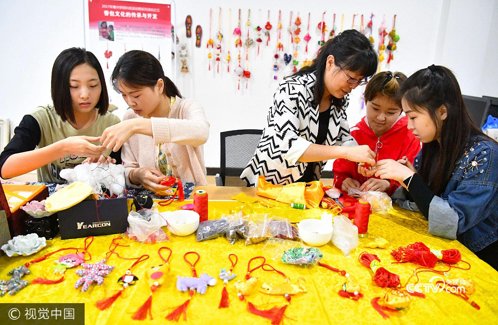 Students from Bozhou College learn to make sachets under the instruction of their teacher Yu Caixia(3rd,L) in Zhumeng Community, Bozhou of Anhui Province, May 23, 2017.