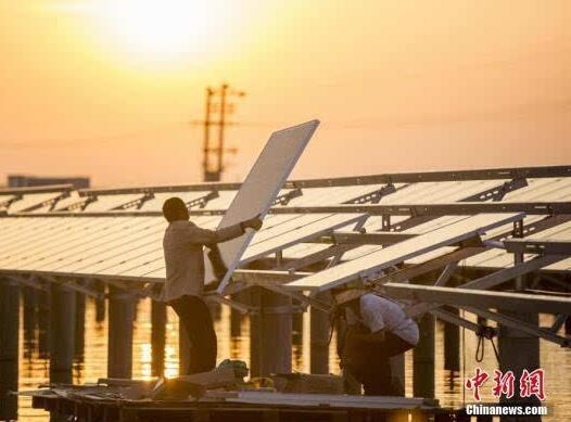 """航拍鄱阳湖畔""""渔光互补""""光伏电站,施工人员安装太阳能光伏板"""