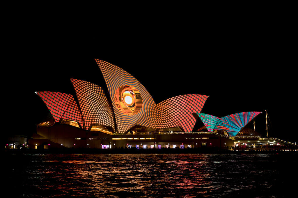 The sails of the Opera House are lit to start the Vivid Festival.