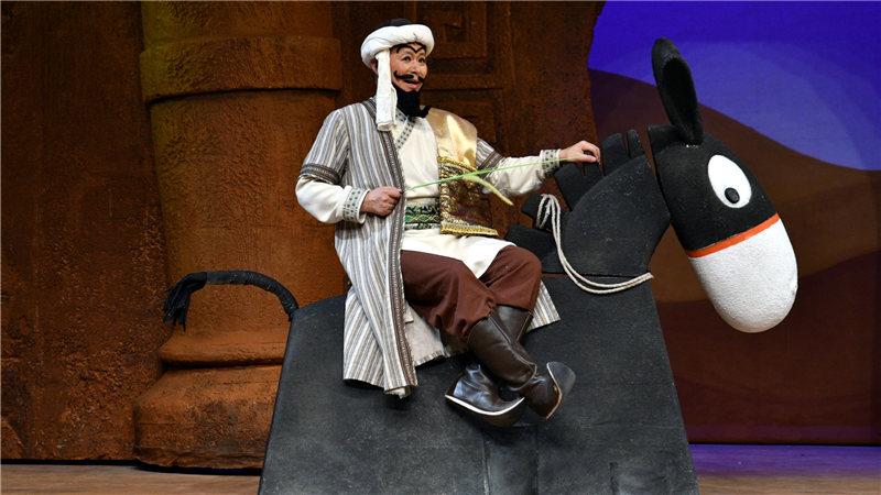 """王宏伟唱着欢快的歌谣""""骑着我的小毛驴"""",坐着一头卡通造型的小黑驴上场"""