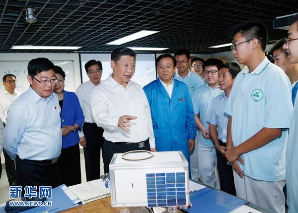 """2016年9月9日,习近平在北京市八一学校实验室察看师生们研制的科普小卫星,他特别对孩子们说:""""你们的小卫星发射时别忘了通知我一下。""""新华社记者鞠鹏摄"""