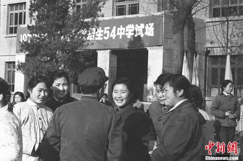 图为1977年12月,北京高考考点的考生们互相交流。 翁乃强 摄 图片来源:视觉中国