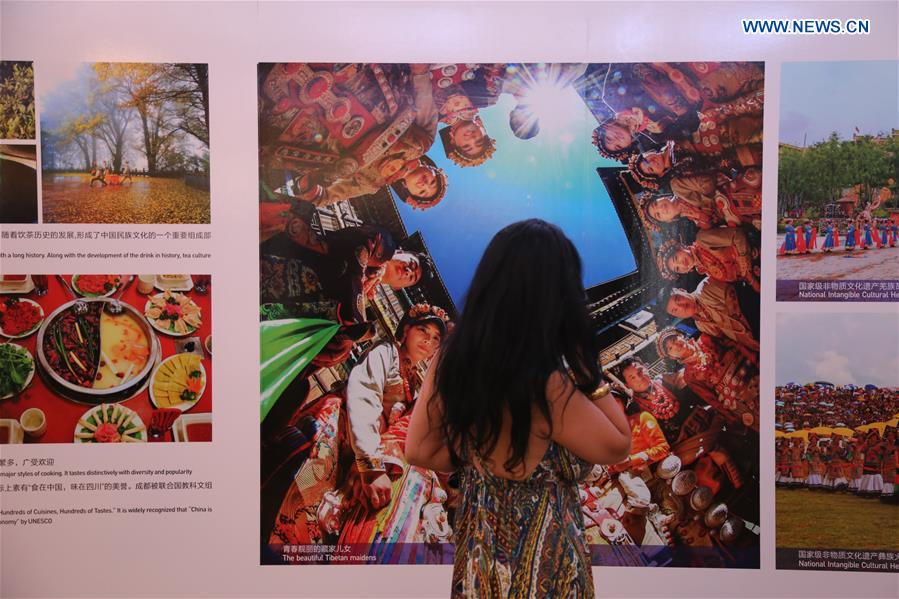 "A woman watches photos displayed at the ""Heaven on Earth, Sichuan in your eyes"" photo exhibition of China"