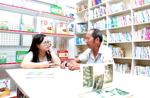 """记者在江西省赣州市安远县车头镇龙头村的""""农家书屋""""里采访前来看书的村民"""