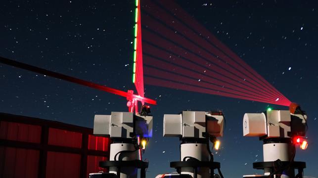 """2016年12月10日,在西藏阿里观测站,""""墨子号""""量子科学实验卫星过境,科研人员在做实验(合成照片)。 新华社记者 金立旺 摄"""
