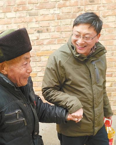 宋伟(右)在村里走访慰问。资料照片