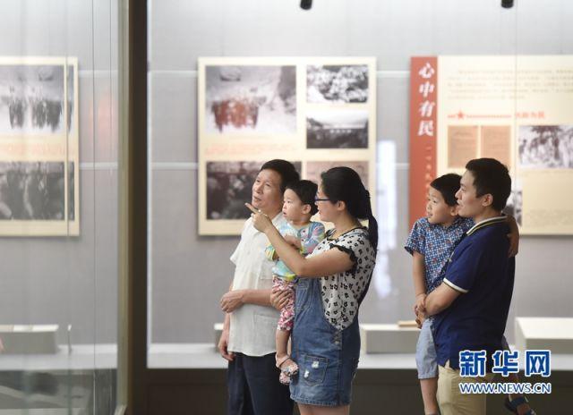 2016年8月16日,福州市台江区的党员林菲(中)与同为党员的丈夫、公公带着两个孩子在参观谷文昌事迹展。(新华社记者宋为伟 摄)