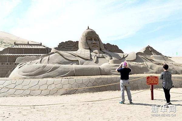 """6月23日,两名游客在观赏2017青海湖国际雕塑与大地艺术旅游季沙雕作品""""格萨尔王""""。"""
