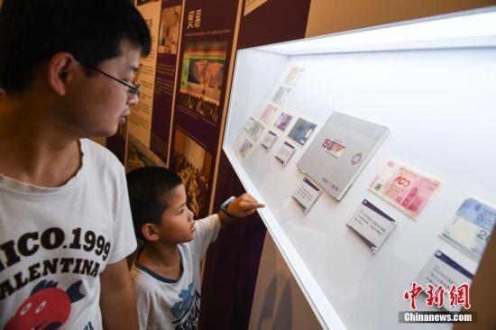 民众参观展出的纪念版港币。 中新社记者 崔楠 摄