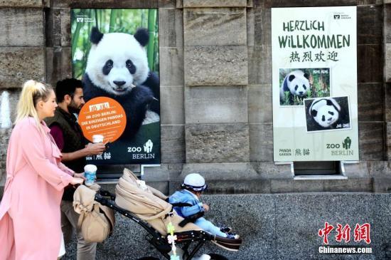 。图为7月4日,一家三口经过柏林动物园外张贴的大熊猫海报。中新社记者 彭大伟 摄
