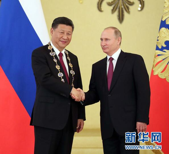 """7月4日,国家主席习近平在莫斯科克里姆林宫同俄罗斯总统普京举行会谈。这是会谈后,普京向习近平授予俄罗斯国家最高勋章""""圣安德烈""""勋章。"""