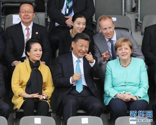 7月5日,国家主席习近平在柏林同德国总理默克尔共同观看中德青少年足球友谊赛。这是习近平和夫人彭丽媛同默克尔在看台上。