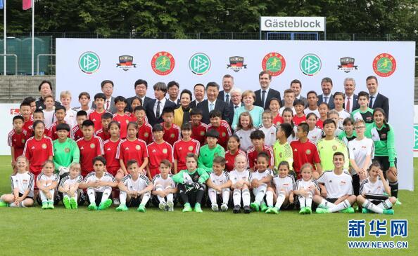 7月5日,国家主席习近平在柏林同德国总理默克尔共同观看中德青少年足球友谊赛。这是习近平和夫人彭丽媛同默克尔与双方小球员合影。