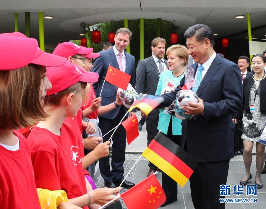 7月5日,国家主席习近平同德国总理默克尔共同出席柏林动物园大熊猫馆开馆仪式。这是习近平向现场的孩子们赠送大熊猫毛绒玩具。-新华社记者谢环驰-摄