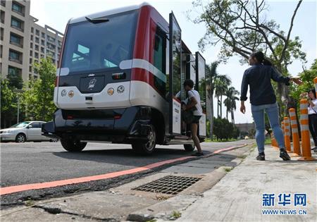 7月10日,试乘游客登上无人驾驶巴士。
