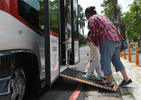 7月10日,无人驾驶巴士放下辅助踏板让儿童上车。
