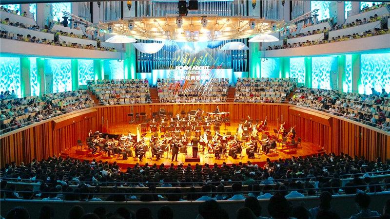 """音乐厅内的穹顶悬挂着数把蓝色小伞,四壁流光溢彩,平日""""高冷""""的舞台变成了一条绚丽浪漫的古典音乐长廊牛小北/摄"""