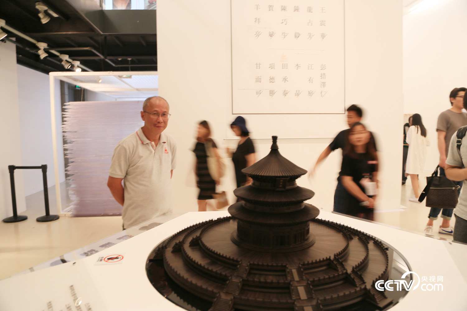 Craftsman Wang Zhenhua and his miniature model of the Hall of Prayer for Good Harvest