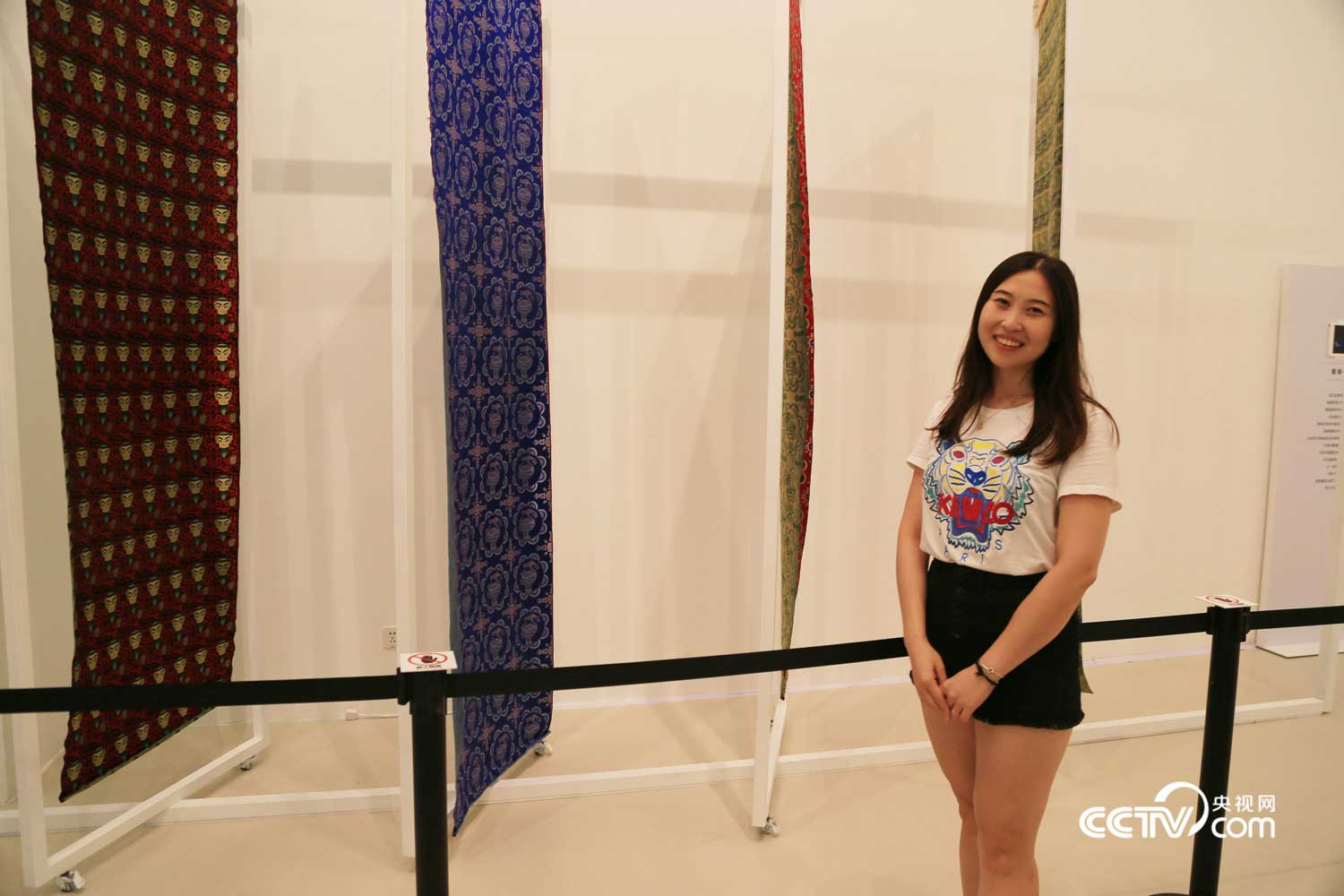 Exhibition visior Ms. Sun poses with Sichuan brocade cloths