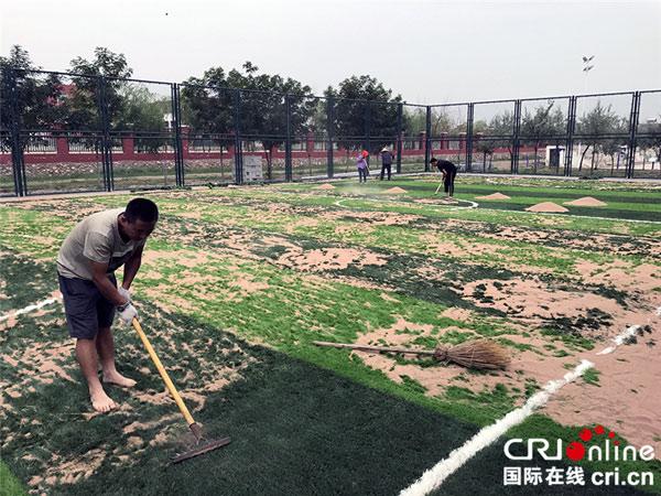 村民正在铺设人造草皮足球场